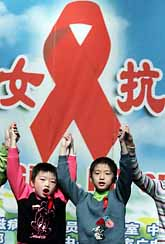 Kinesiska barn under världs-aidsdagen. Barnen har förlorat någon förälder i aids. Rosetten är en symbol för sjukdomen aids. Foto: Pressens Bild