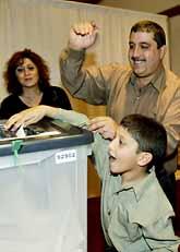 Irakierna Susan och Simon Atty med sonen Joseph röstar. Det är första gången för dem. De röstade i staden Irvine i USA. Foto: Ric Francis/Pressens Bild