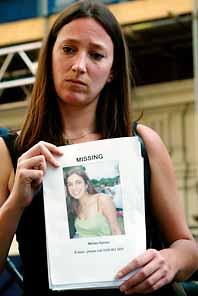 Kvinnan heter Melissa Lehrer. Hon håller upp en bild på en vän, Miriam Hyman. Miriam saknas efter bombdåden. Minst tjugo människor saknas. Foto: Pressens Bild