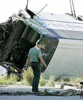 En spansk polis står vid den välta bussen. Tre personer dog vid olyckan på ön Teneriffa. Foto: Ramon de la Rocha/Pressens Bild