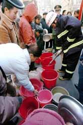 Brandmän delar ut vatten till folket i Harbin. Foto: Pressens Bild