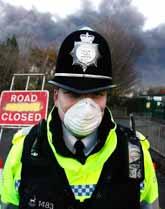 En polis vaktar i närheten av branden i bränslelagret i Storbritannien. Foto: Cathal McNaughton/PrB