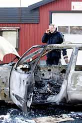 En polis undersöker en av rånarnas bilar. Rånarna eldade upp dem för att förstöra alla spår. Foto: Björn Larsson Rosvall/PrB