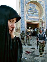 En irakisk kvinna utanför den sprängda moskén. Kvinnan talar i mobiltelefon. Kanske berättar hon för oroliga släktingar att hon inte blev skadad i bombdådet. Foto: Khalid Mohammed/Pressens Bild
