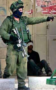 En israelisk soldat framför en gripen palestinier. Foto: Pressens Bild