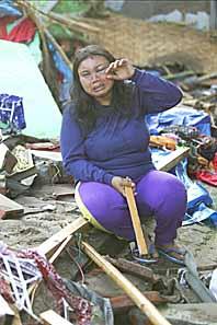 En kvinna sitter bland bråten på stranden. Flodvågen i Indonsien dödade minst trehundra personer. Foto: Dita Alangkara/PrB