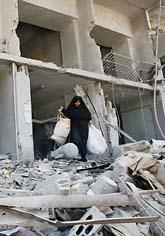 En kvinna bär ut sina ägodelar från ett bombat hus. Foto: Dimitri Messinis/Scanpix