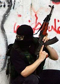 En maskerad Hamas-soldat  gömmer sig bakom en husvägg i staden Gaza City. Foto: Eyad Albaba/PrB
