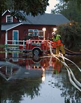 Claes Kämpe i Aneby jobbar med att få undan regnvatten vid en villa. Foto: Johan Nilsson/Scanpix