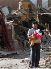En man bär på sitt barn utanför ett hus som rasat i staden Pisco i Peru. Foto: Martin Mejia/AP/Scanpix