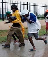 Några människor springer för att ta skydd i Jamaicas huvudstad Kingston. Foto: Anders Leighton/AP Photo/Scanpix