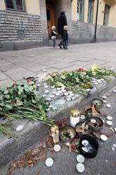 Blommor och ljus på trottoaren i Stockholm där en 16-årig pojke blev misshandlad till döds. Foto: Fredrik Sandberg/Scanpix