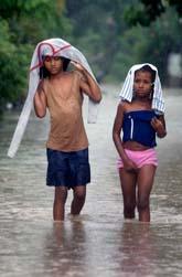 Två flickor i Dominikanska Republiken går i översvämningarna. Foto: Ramon Espinosa/AP Photo/Scanpix