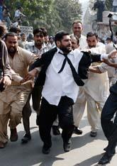 Poliser i vanliga kläder jagar och griper domare som protesterar mot presidenten. Foto: K M Chaudary/Scanpix
