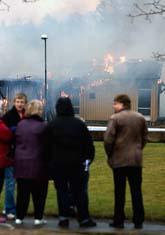 Några elever har samlats framför den brinnande skolan. Foto: Adam Ihse/Scanpix