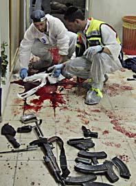 Räddningsarbetare undersöker platsen där terroristen sköts till döds. Foto: Shin Mesh/Scanpix