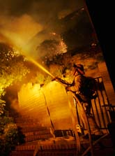 En brandman i Kalifornien spolar vatten på ett hus för att skydda det från bränderna. Foto: Dan Steinberg/Scanpix