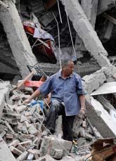 En man i ruinerna av ett rasat hus i Kina. Tusentals människor är begravda under rasade hus. Foto: Scanpix