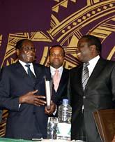 Robert Mugabe och Morgan Tsvangirai tittar på varandra och ler. De ska dela makten i Zimbabwe. Foto: Tsvagirayi Mukwazhi/Scanpix