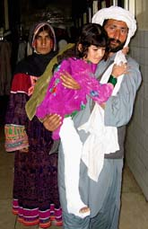Pakistanska föräldrar bär en dotter som skadades i jordbävningen. Foto: Shah Khalid/Scanpix.