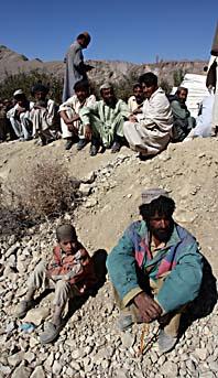 Människor i Pakistan väntar på att få filtar att värma sig med efter jordbävnignen. Foto: Shakil Adil/Scanpix.