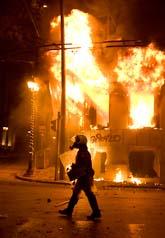En grekisk polis utanför ett brinnande hus i Aten. Foto: Petros Giannakouris/Scanpix.