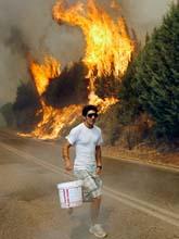 En man har hämtat en hink vatten för att hjälpa till att släcka bränderna. Foto: Dimitri Messinis/Scanpix