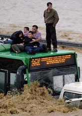 Några passagerare har tagit sig upp på bussens tak för att komma undan regnet. Foto: Ibrahim Usta/Scanpix
