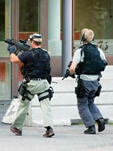 Poliser med vapen undersöker penga-lagret i Stockholm efter rånet. Foto: Pontus Lundahl/Scanpix
