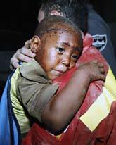 Tvåårige Redjeson Hausten har räddatas ur ett av de rasade husen. Foto: Gerald Herbert/Scanpix