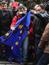 Demonstranter i Grekland bränner en EU-flagga. Foto: Thanassis Stavrakis/AP/Scanpix