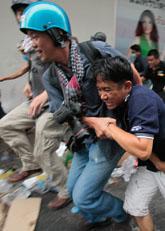 En skadad demomstrant i Bangkok får hjälp av en fotograf. Foto: Sakchai Lalit/Scanpix