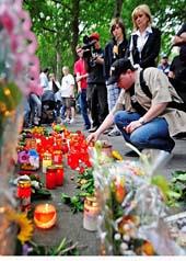 Människor tänder ljus och sörjer de dödade på musikfesten.  Foto: Clemens Bilan/Scanpix