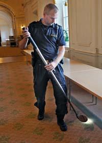 En polis undersöker området utanför ett av riksdagens mötesrum. Foto: Bertil Ericson/Scanpix