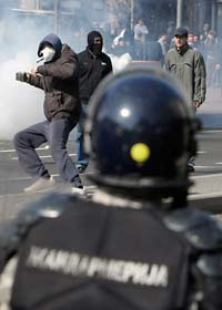 Motdemonstranter i Belgrad kastar stenar på poliserna. Foto: Darko Voijnovic/Scanpix