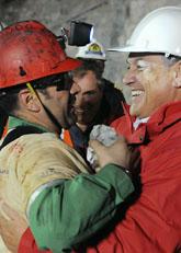 En av de räddade gruvarbetarna kramas om av presidenten. Foto: Jose Manuel  de la Maza/Scanpix