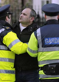 Poliser stoppar en man utanför Irlands parlamant. Han är en av många som protesterade mot regeringens sparplaner. Foto: Niall Carson/Scanpix