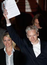 Julian Assange visar lappen som talar om att han får lämna häktet. Foto: Kirsty Wigglesworth/Scanpix