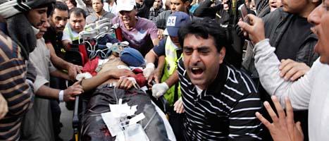 En skadad demonstrant ligger på en bår efter polisens attack i Bahrain.