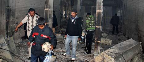 Libyer i ett utbränt hus i staden Benghazi. Foto: AP/Scanpix