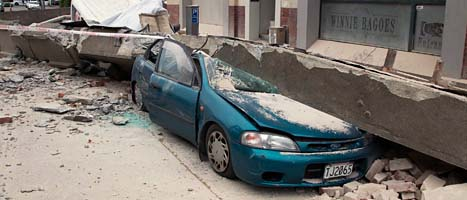 En bil har krossats av en bjälke från ett hus. Jordbävningen i Christchurch dödade minst 65 människor. Foto: Mark Mitchell/Scanpix