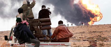 Rebeller på väg mot striderna. I bakgrunden har ett bränsle-förråd exploderat. Foto: Hussein Malla/Scanpix