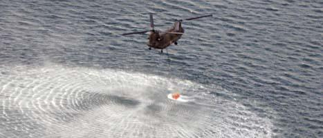 En helikopter hämtar vatten i havet för att försöka släppa ner det över de skadade reaktorerna. Foto: Yomiuri Shimbun, Kenji Shimizu/Scanpix