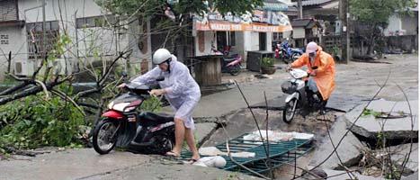 Turister försöker komma fram på en skadad väg på ön Koh Samui. Foto: Apichart Weerawong/Scanpix