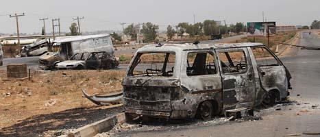 Uppbrända bilar är spår som syns efter striderna i Nigeria. Foto: Sunday Alamba/Scanpix