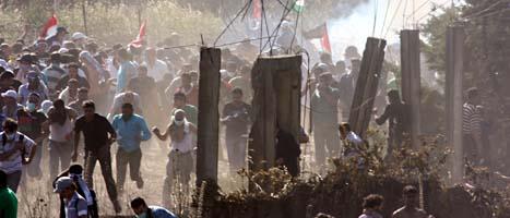 Demonstranterna flyr när Israels soldater sprutar tårgas på dem. Foto: Bassem Tellawi/Scanpix
