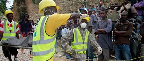 Räddningsarbetare bär bort en man som dödats i ett jordras i Haiti. Foto: Dieu Nalio Chery/Scanpix