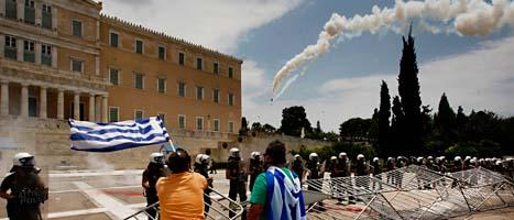 Polis skjuter med tårgas mot demonstranter utanför parlamentetshuset i Aten. FOTO: Petros Karadjias/Scanpix