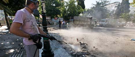 Spåren efter bråken städas bort från Atens centrum. Protesterna mot sparförslagen har varit våldsamma. Foto: Dimitri Messinis/Scanpix