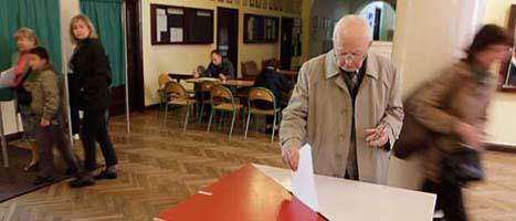 En man i Polens huvudstad lägger sin röst i valet till parlamentet. Foto: Czarek Sokolowski/Scanpix